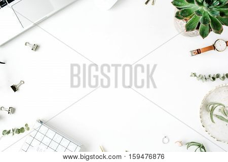 Flat lay top view office table desk frame. feminine desk workspace with laptop diary succulent glasses watch on white background.