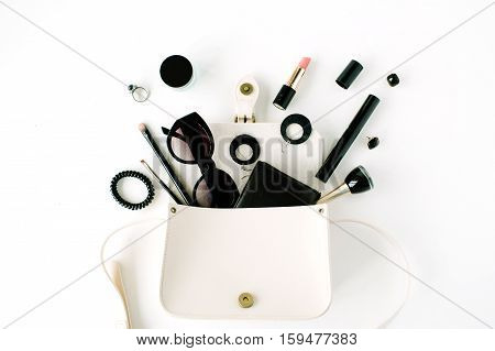 flat lay feminine arrangement with wallet accessories purse cosmetics sunglasses on white flat lay top view