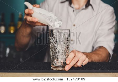 Barman's hands in bar interior making alcohol cocktail. Professional bartender at work mixing ice in glass for drink. Party time in night club