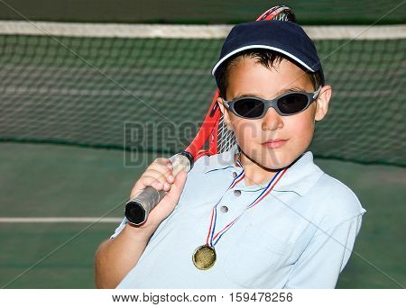 Little boy with hat and racket in his shoulder after a night tennis game posing