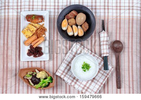 Rice gruel served with dish of sausage spicy clams ,sweet radish omelet and spicy caned mackerel and fried mixed vegetable and dish of stewed boiled egg.