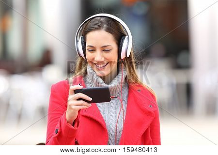 Front view of a happy girl watching videos on line in a smartphone or listening music walking towards camera in the street