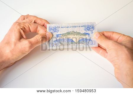 Man holding one Bhutanese Ngultrum banknote in his hands