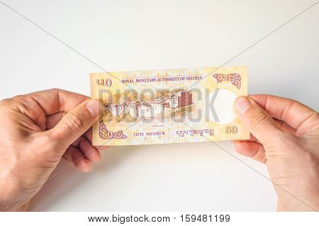 Man Holding Fifty Bhutanese Ngultrum Banknote In His Hands