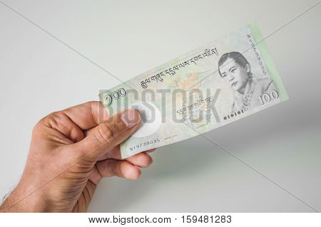 Man Holding Hundred Bhutanese Ngultrum Banknote In His Hand