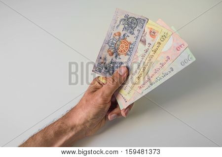 Man Holding A Bunch Of Bhutanese Ngultrum Banknotes In His Hand