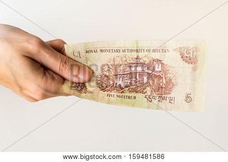 Woman Holding Five Bhutanese Ngultrum Banknote In Her Hand