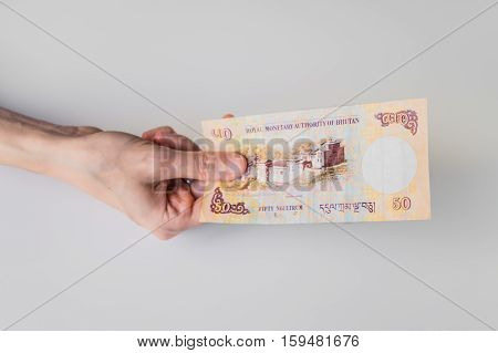 Woman Holding Fifty Bhutanese Ngultrum Banknote In Her Hand
