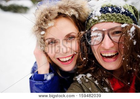 Faces of two young women are closed up with snow. They play with someone in snowballs. Women delighted with fight. They cheerfully laugh.