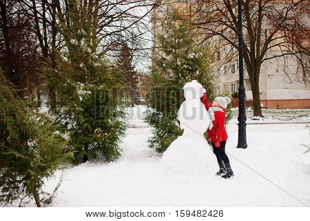 The girl of school age builds a snowman. On the ground there is a lot of snow. The girl in a red jacket and a gray knitted cap stands near a big snowman. She decorates the head of a snowman.