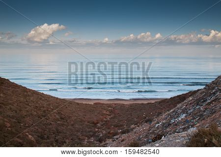 Atlantic Ocean in an early morning. Cloudy sky. In the foreground hills with a lot of rubbish. Sidi Ifni Morocco