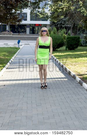 the beautiful woman in a green dress goes on the sidewalk a subject beautiful women in the city in the summer
