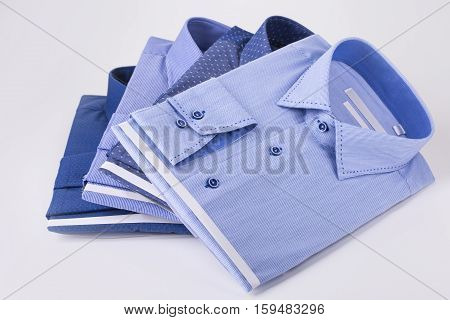 Four men's shirts are a pile on a white background