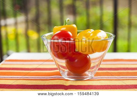 Healthy vegetables in a bowl on the table covered with a tablecloth with stripes in the green garden. Yellow peppers and red tomatoes with vitamins are a very good choice for a healthy diet. Natural light and good mood.