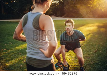 Female trainer guiding man while exercising with kettlebell in park. Personal trainer with man doing weight training in park.