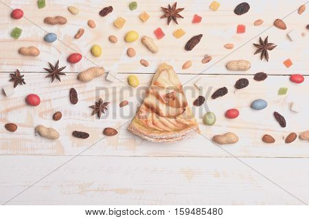 Single slice of apple pie with mix of colorful dragee marmalade or jelly candies almonds peanuts raisins anise sugar cubes on vintage wooden background