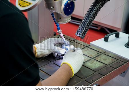 Worker using repair mold and die part by Laser welding machine in factory.