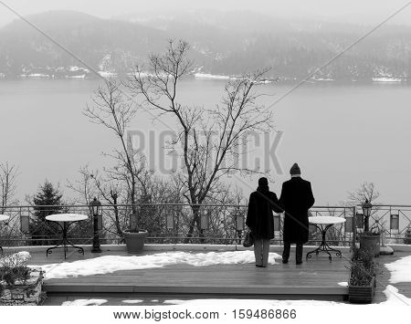 Elder Couple holding each other while standing and staring the cold lake. Greece