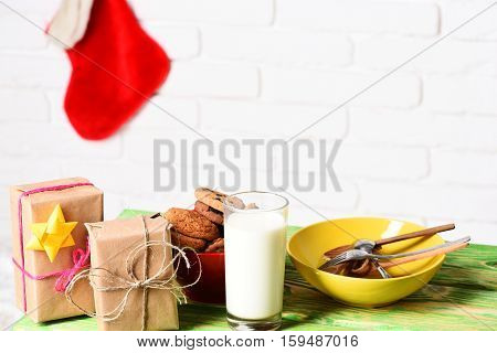 wooden green table with milk gifts wrapped in craft paper and chocolate chip cookies near yellow bowl with decorative christmas or xmas stocking or boot on white brick wall background