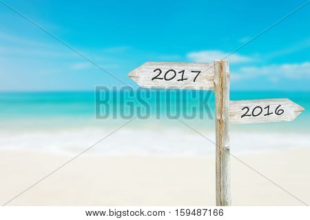 Wooden Blank Sign With Text 2017 Over Blurred blue sea and sand beach with Cloudy Blue Sky Image for New year 2017 Concept.