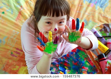 Cute little girl with painted hands .