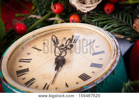 Green mistletoe and old clock on wood desk. Nature background. Christmas plant.