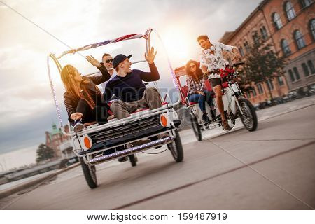 Group of friends having fun with two tricycles on road. Teenagers on tricycle ride on city street.