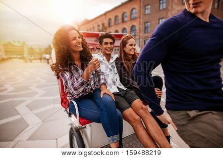 Group of friends having fun on tricycle ride in the city. Young people traveling on tricycle.