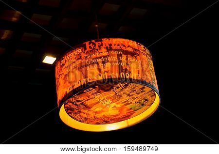 Orange round stylish lampshade with differnet words and messages hang from ceiling in black background