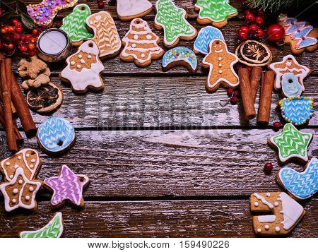 Christmas gingerbread cookies on woden table and candels. Frame with ginger snap and cinnamon sticks. Copy spice with wooden place for text or wishes.