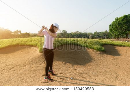 Asian woman golf player hitting golf ball out of sand trap. Golf sport concept.