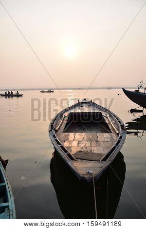 Boat floating on river Ganga during sunrise in Varanasi, Uttar Pradesh, India