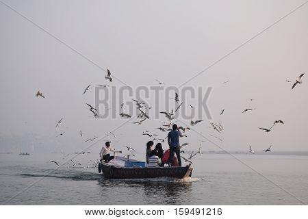 VARANASI, UTTAR PRADESH, INDIA - FEBRUARY 17 - Boat with tourists and birds on river Ganga