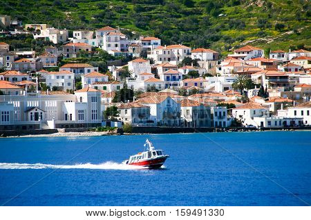 Small red motor boat transfer people to Spetses island Greece