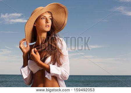 Beautiful girl enjoys hot sunny day at the beach.