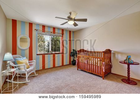 Bright Colorful Nursery Room With Contrast Striped Wall
