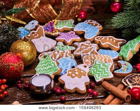 Christmas gingerbread cookies on woden table and candels with Christmas ribbon.