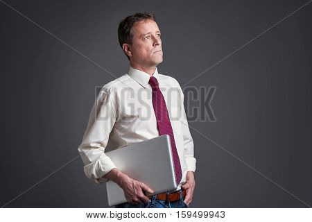 A middle age man standing with a laptop and looking sideways