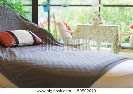 resting seat with pillow near to a cozy balcony in the morning
