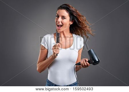 A beautiful young woman feeling happy and singing while using a hairdryer and a hairbrush.