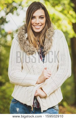 Closeup outdoors portrait of beautiful young blonde Caucasian woman in knit sweater in autumn in park, posing, smiling, looking at camera. Medium retouch, vibrant colors.