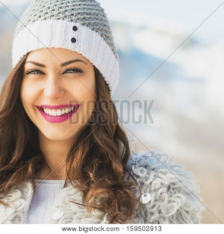 Closeup of gorgeous young brunette woman in knitted beanie hat in winter, posing, smiling, outdoors on snowy day in mountains. Closeup, copy space, retouched.