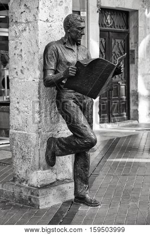 Burgos Spain - August 29 2016: Statue or the newspaper reader next to Plaza Mayor square in Castilla Spain