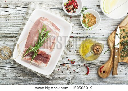 A piece of pork in the form of steam before baking in the oven. Ingredients for marinating meat, rosemary, salt, spices, olive oil, hot pepper. Top view