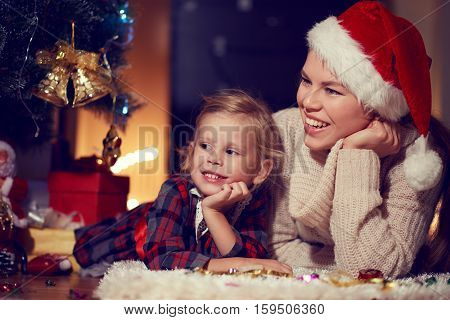 Family Christmas tradition concept. Cute smiling girl lying on snug carpet with her mom looking together at New Year tree decoration.
