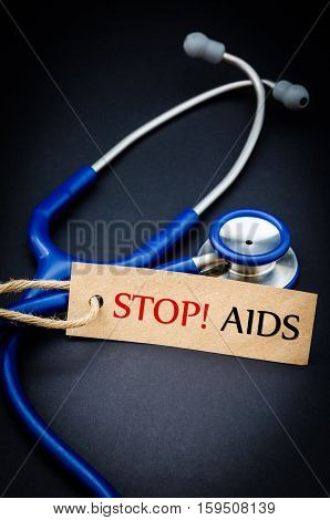Stop AIDS in paper tag with stethoscope on black background - health concept. Medical conceptual