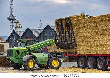 VARNA, BULGARIA September 19.2016: JohnDeere Telescopic handler unloading bales from truck. Day view
