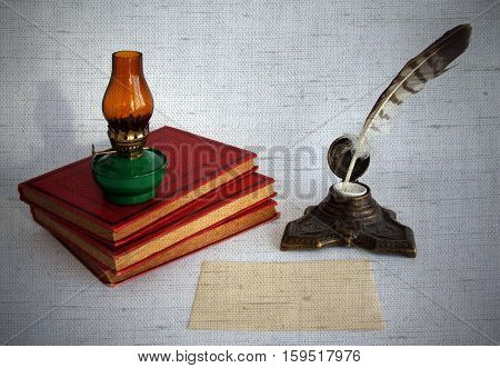 Blank paper card oil lamp and inkwell with a quill pen as a concept of writing letters and greetings on holidays. Photos with the effect of natural canvas.