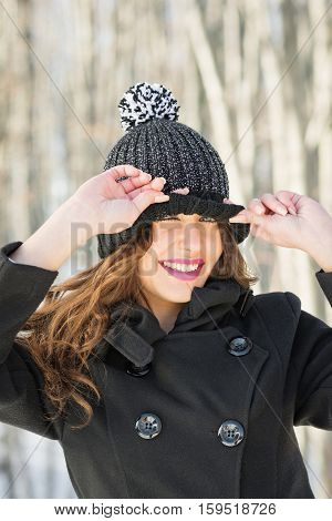 Closeup portrait of beautiful young woman in black knitted beanie hat and coat outdoors in winter, smiling, posing. Mild retouch.