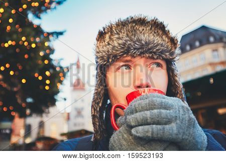 Young man drinking hot wine (or punch or tea or coffee) from red cup at the Christmas market - Munich Germany